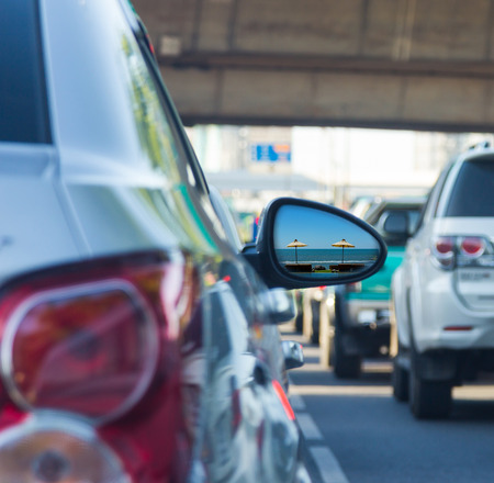 Sea view in side mirror of car with traffic jam  Stock Photo