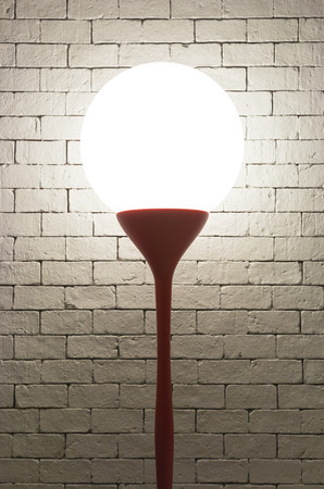 Lamp with circle shape on white bricks background vertical