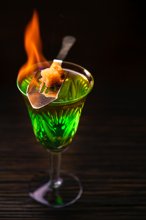 Blazing absinthe with sugar pieces on special spoon. Vertical studio shot. Stock Photo