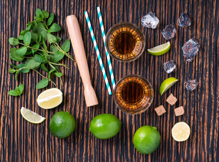 bartending: Wooden counter with glasses and fresh limes with mint leaves ready for preparation of alcoholic mojitos.