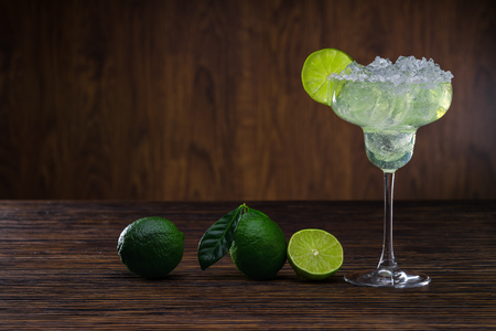 bartending: Glass of classical Margarita cocktail with ice and slice of lime on wooden table with fresh limes. Stock Photo