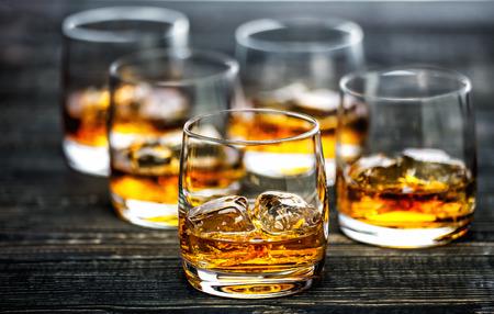 Glas Schotse whisky en ijs op een zwarte houten achtergrond, selectieve nadruk