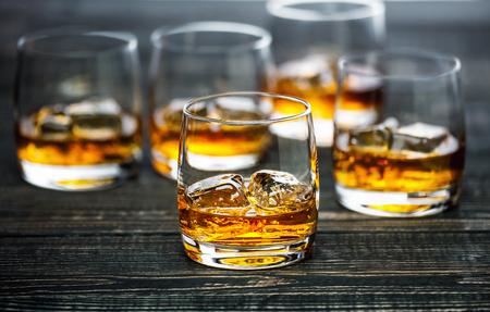 Glas Schotse whisky en ijs op een zwarte houten achtergrond, selectiv-nadruk Stockfoto