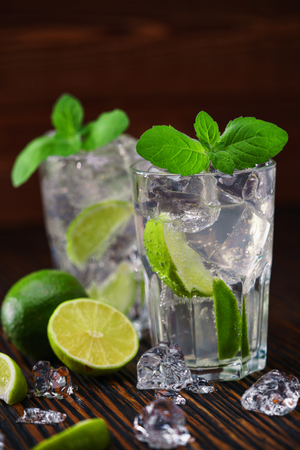 bartending: two glasses with  non-alcoholic mojito cocktail  served with limes and ice on a wooden background,selective focus