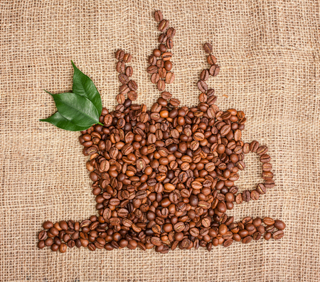 cup of coffee from beans with leaves on sackcloth background
