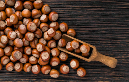 hazelnut in brown bowl on textured wooden background, top view.