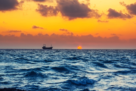 Seascape with cargo ship in sunset time, in the Mediterranean Sea Stok Fotoğraf