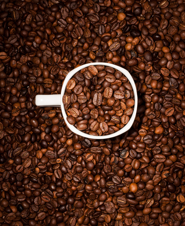White cup full of coffee beans on Roasted Coffee Beans background