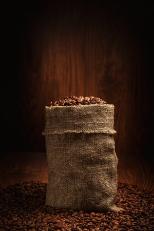 bag filled with coffee beans in spotlight on a wooden background 스톡 콘텐츠