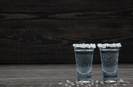 Cold silver tequila with white salt crystals in lime on a black wooden background
