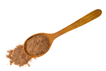 cinnamon powder in wooden spoon isolated on white background,macro shot Imagens