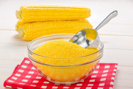 corn grits in a transparent plate with ears of corn on the wooden background Stock Photo