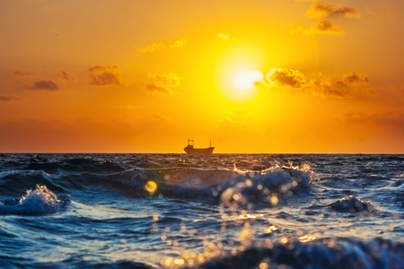 Cargo ship at sunset in the Mediterranean Sea Stok Fotoğraf