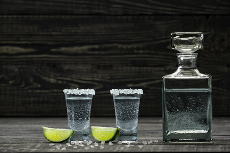 Two glasses cold silver tequila with lime on a black wooden background