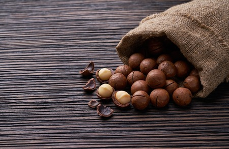 Macadamia nuts in bag  on brown wooden table .
