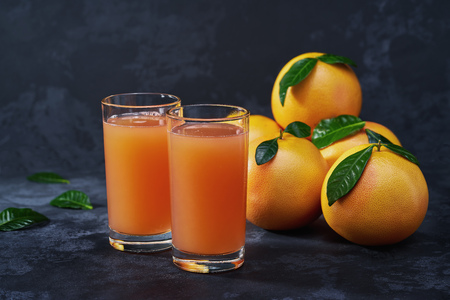 Glass of fresh grapefruit juice on on a black background with copy space background