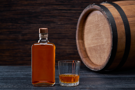 Glass of whiskey background of barrel and  old table of wood.Whiskey drink. 免版税图像