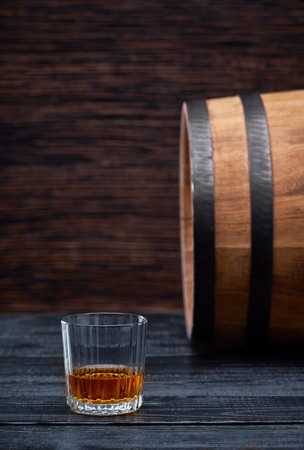 Whiskey on a  black wooden background.Traditional old wooden barrels