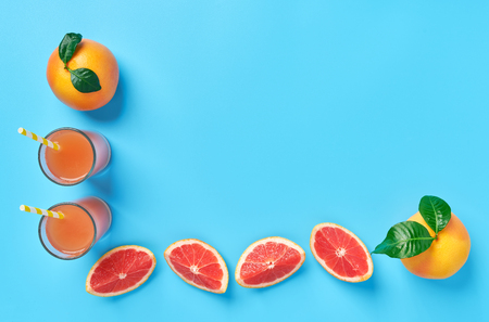 Frame of grapefruit juice and ripe grapefruits on a blue background ,top view