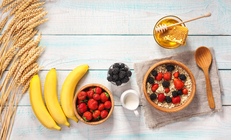 Healthy breakfast with oat flakes and fresh berries on rustic background.Top view Stockfoto - 112269911