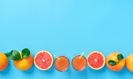 Linear composition of slices of ripe grapefruit with glass of grapefruit juice on a blue background with copy space Stock Photo