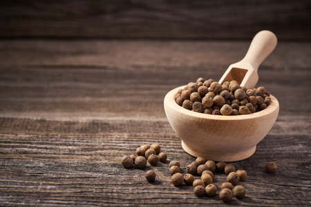 Allspice on a gray wooden background. 免版税图像