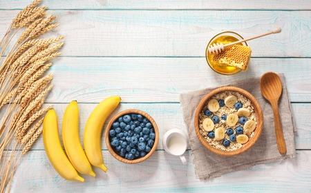Gesundes Frühstück mit Haferflocken, Naturmilch, frischer Banane, Mandeln und Honig. Rustikaler Hintergrund. Ansicht von oben.