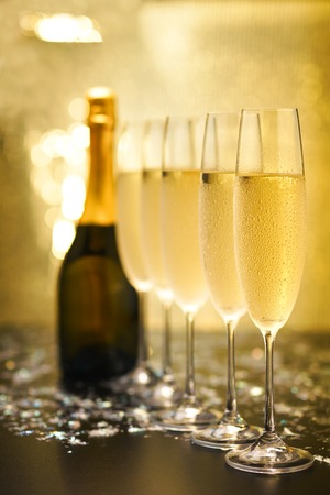 Many glasses of champagne in a line. Gold background