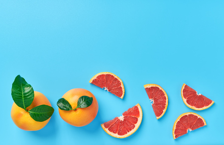 Two grapefruit with  green leaf and grapefruit slices on a blue background,top view