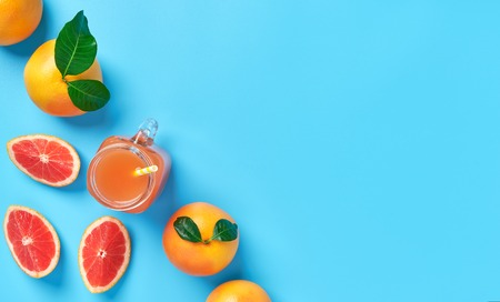 Organic grapefruit juice and  ripe half of grapefruit  on a blue background,top view