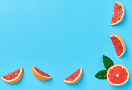 Ripe half of pink grapefruit on a blue background.top view