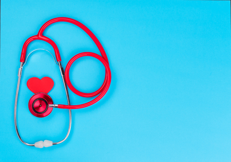 Red stethoscope  on blue table background with copy space for  text. Medicine concept