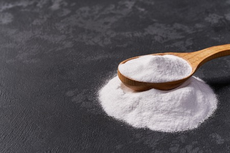 Baking soda in a wooden spoon on a black background .