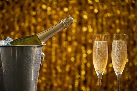bottle of champagne in a bucket with ice  and two glasses of champagne on Christmas and New Years holiday background .Celebration theme with champagne still life