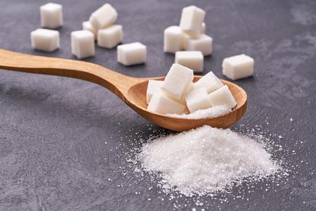 white sugar in wood spoon on black table,selective focus Banco de Imagens