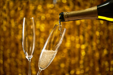 Pouring champagne into glass on golden stylish background Imagens