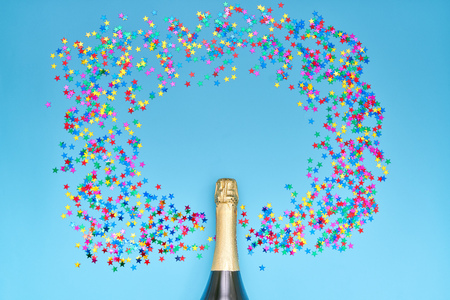 Creative photo of champagne bottle with colorful confetti on blue  background. Flat lay of christmas, anniversary, new year celebration concept