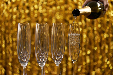 Many glasses of champagne on the table in the restaurant.The process of bottling champagne in glasses.