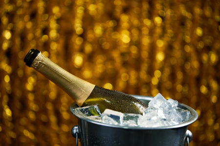 bottle of champagne in a bucket with ice on Christmas and New Years holiday background Banco de Imagens