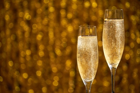 two glasses of champagne on golden stylish background with golden bokeh circles place for text