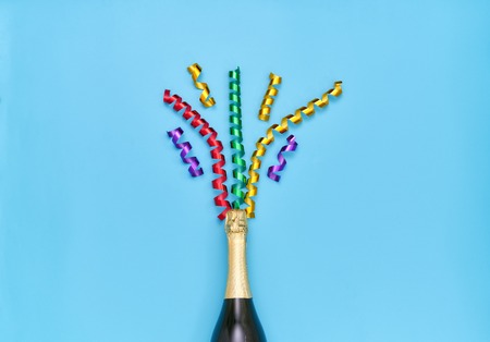 Champagne bottle with colorful party streamers on a blue background