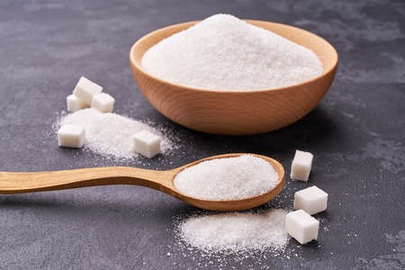 Bowl and  wooden spoon full of  white sugar on black background Banco de Imagens