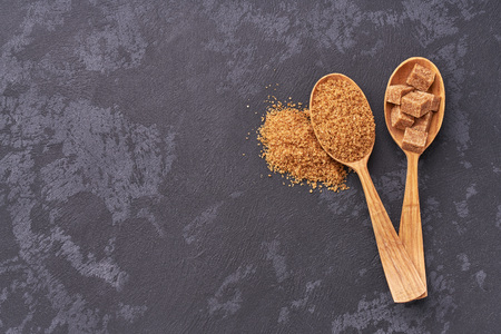 Brown sugar cubes  and granulated sugar  in two wooden spoons with white sugar on  black table.Top view