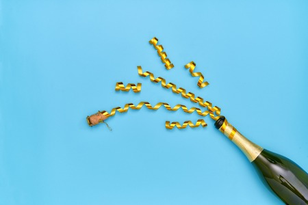Champagne bottle with goldenparty streamers on a blue background 写真素材