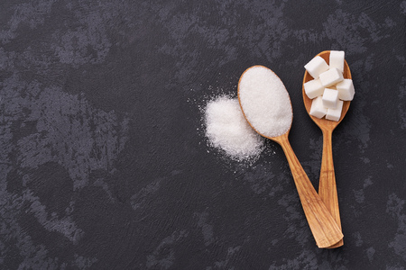 White sugar cubes  and granulated sugar  in two spoons with white sugar on  black table.Top view Banco de Imagens