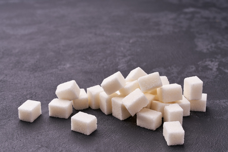 White sugar cubes  on black table close-up.