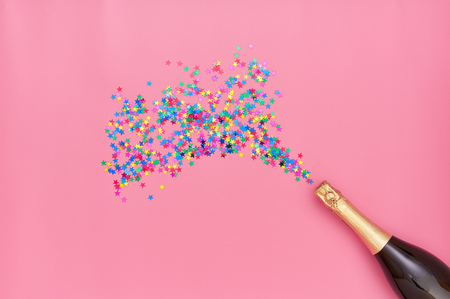 Creative photo of champagne bottle with colorful confetti on pink  background. Flat lay of christmas, anniversary, new year celebration concept