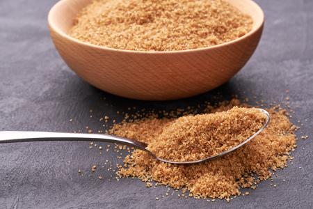 Close-up of granulated brown  sugar in metal spoon