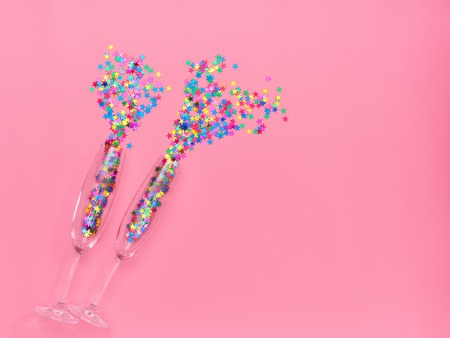Two champagne glasses with colorful confetti  on pink  background. Flat lay, top view celebrate party concept