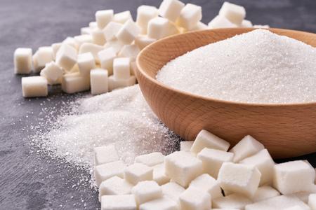 White sugar in wooden bowl, White sugar in background. Sugar cubes